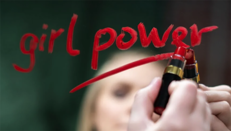 """Woman writing """"girl power"""" on a mirror with red lipstick (For NCOSE article: """"No"""